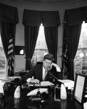 President John F. Kennedy seated at the Resolution Desk