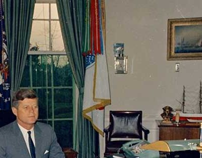 President John F. Kennedy at his desk in the Oval Office