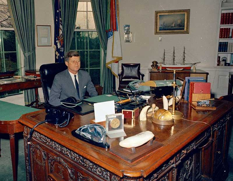President John F Kennedy At His Desk In The Oval Office